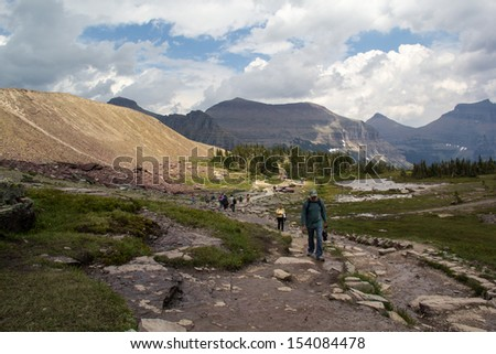 GLACIER NATIONAL PARK, MONTANA,USA-JULY 27: Visitors hike a trail in Glacier National Park on July 27, 2013. The park is the center of one of the largest and most intact ecosystems in the USA.