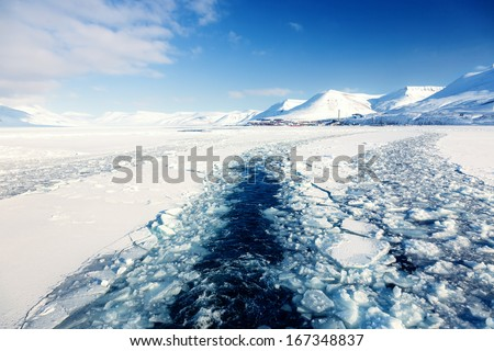 Glacier with small iceberg at the Arctic North Pole, Svalbard.In background is Longyearbyen city