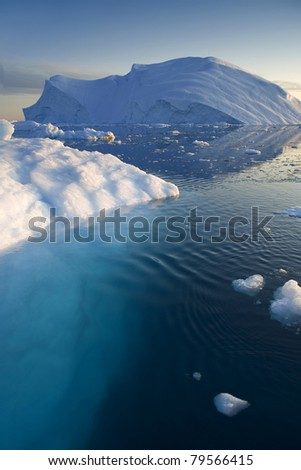 Glaciers and icebergs of Greenland. There are smaller pieces of ice in the foreground.