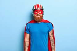Glad bearded man with funny outlook, comes on costume party, being superhero character, wears helmet, mask and red cloak, has fun with friends, poses against blue background. Save world concept
