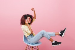 Glad brunetteIndoor full-length portrait of confident african girl in pink shirt holding skateboard. Enthusiastic black woman with curly hairstyle posing in studio with blue interior. in black sneaker