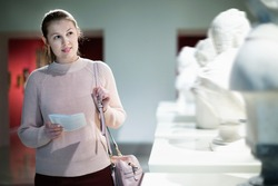Glad cheerful girl looking with interest at ancient sculptures in museum, using guidebook