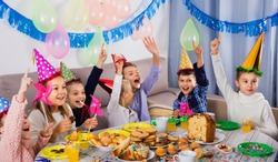 Glad cheerful positive smiling boys and girls behaving jokingly during friend birthday party
