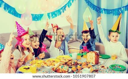 Glad cheerful positive smiling boys and girls behaving jokingly during friendâ??s birthday party