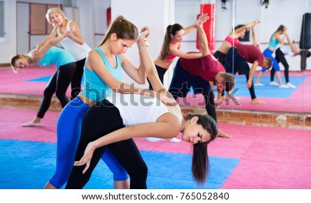 Glad cheerful positive women are doing self-defence moves in pairs in sporty gym. Stock photo ©