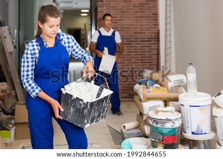 Glad cheerful smiling man and woman in work overalls doing finishing work in room of public space