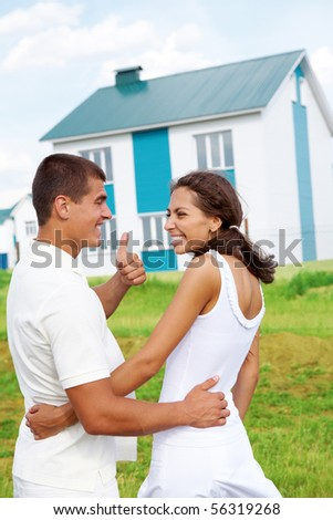 Glad couple smiling at each other while guy showing thumb up with nice house outdoors