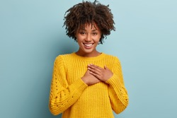 Glad dark skinned woman with Afro haircut, keeps hands on heart, dressed in yellow jumper, expresses gratitude, has friendly facial expression, isolated over blue background. I promise to be loyal