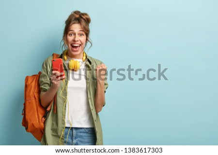 Glad female blogger clenches fist, feels excited from statistics on web page in social networks, uses cell phone and headphones, wears khaki shirt and jeans, carries backpack, isolated on blue wall #1383617303