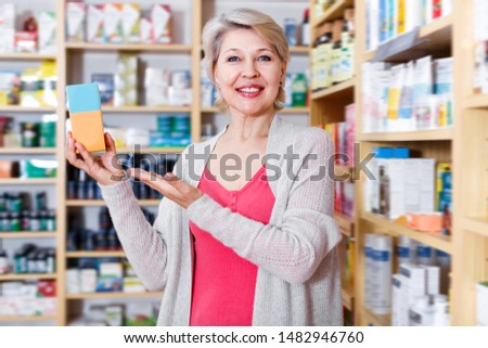 Glad female customer looking for products of skin care in specialized shop