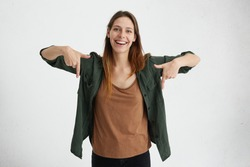 Glad female with oval face, dark straight hair wearing green jacket and brown shirt pointing with her index fingers down having cheerful look while advertising something. Advertising concept