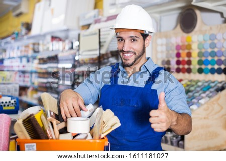 glad foreman standing near racks in paint store holding basket with tools