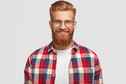 Glad ginger male with pleased expression, wears glasses and fashionable checkered shirt, rejoices successfully made project, poses alone against white background. People, emotions, lifestyle