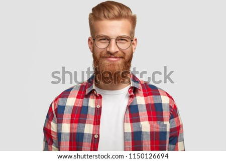 Glad ginger male with pleased expression, wears glasses and fashionable checkered shirt, rejoices successfully made project, poses alone against white background. People, emotions, lifestyle #1150126694