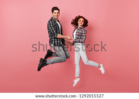 Glad girl having fun with boyfriend. Studio shot of couple fooling around in valentine's day.