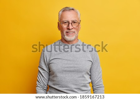 Glad grey haired man with satisfied expression has good mood wears optical glasses and casual jumper poses against vivid yellow background. Happy senior male model has pleasant conversation.