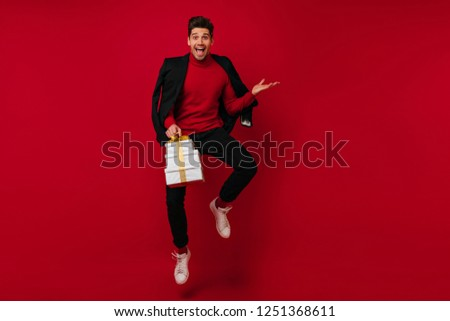 Glad guy with new year presents funny dancing on red background. Cheerful white male model fooling around in christmas in studio.