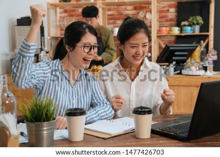 glad joyful positive freelance women coworkers looking at screen of laptop computer with raised hands and fists shouting screaming celebrating victory in modern coffee shop. bartender work in cafe #1477426703