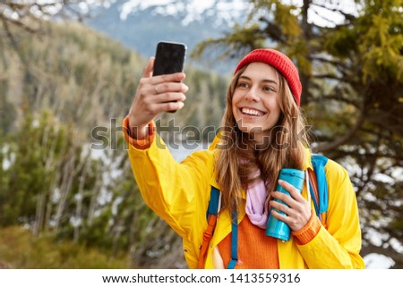 Glad lovely dark haired girl makes selfie portrait on cell phone, dressed in raincoat, headgear, wanders and explores world, drinks coffee from flask, poses in forest against mountains near river
