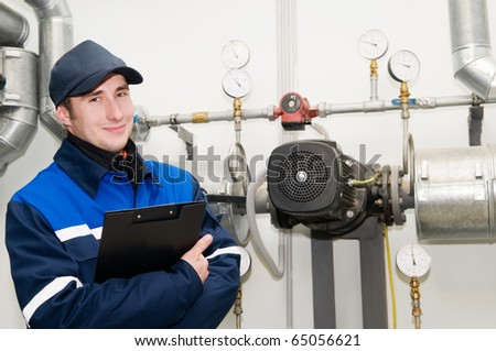 glad maintenance engineer checking technical data of heating system equipment in a boiler room