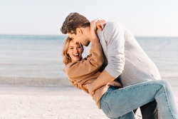 Glad man dancing with girlfriend on sea background. Glamorous girl with wavy hair posing at beach with friend.