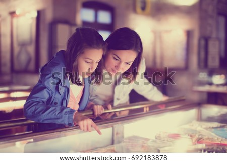 Glad mother and daughter exploring expositions of previous centuries in museum