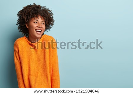 Glad overemotive dark skinned lady with curly hairstyle, laughs happily, expresses sincere emotions, being amused by friend, dressed in orange casual jumper, models in studio alone with mockup space #1321504046