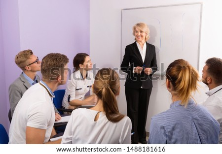 Glad pleasant female speaker giving presentation for smiling students in lecture hall  #1488181616
