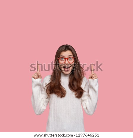 Glad pleased brunette woman shows perfect space upstairs, wears oversized white sweater, indicates up with both index fingers, isolated over pink background. Hey, follow this direction, please
