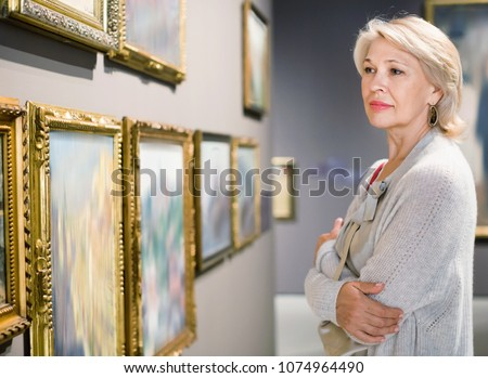 Glad  positive smiling female visitor looking at artwork painting in the museum indoors
