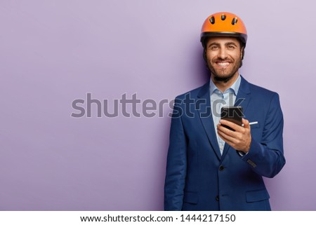 Glad satisfied male engineer wears protective headgear, elegant formal suit, ready for meeting with colleagues, holds mobile phone for chatting online, isolated on purple background, blank space