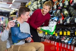 Glad seller woman is helping male to trying on ski boots in sport shop.