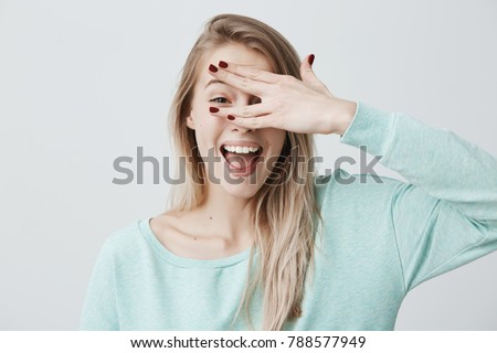 Glad smiling blonde female model hiding her face behind hand, has broad smile, happy to recieve compliments from handsome man, isolated against gray background. Positive young woman