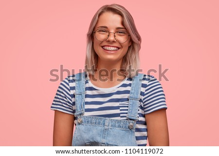 Glad smiling pretty female freelancer, has broad smile, demonstrates teeth with braces, wears casual t shirt with overalls, rejoices recieving reward, stands against pink background. Emotions concept #1104119072