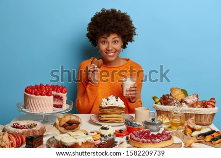 Glad smiling woman with Afro curly hairdo eats tasty pastry with milk, has good mood to eat delicious desserts, tries yummy just baked cookies, cannot loose weight because of sugar addiction