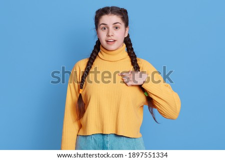 Glad surprised woman points at herself with fingers, cannot believe, being chosen for something, opens eyes widely, wears yellow jumper and jeans, posing isolated over blue background. Stock photo ©