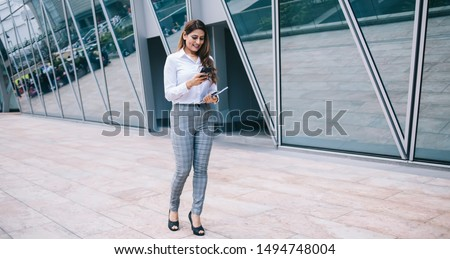 Glad trendy ethnic woman in comfy formal wear standing in megapolis near modern urban building with notebook and using smartphone ストックフォト ©