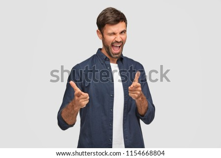 Glad unshaven male blinks with eye, opens mouth and points at camera, feels excited, wears casual clothes, demonstrates his choice, stands against white background. Joyful European man indoor