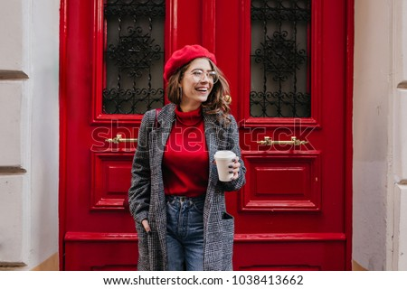 Glad white female model in long gray jacket looking away with smile standing near red door. Outdoor photo of beautiful caucasian woman in sweater drinks coffee in front of cafe and laughing. #1038413662