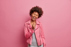 Glad young African American woman sings favorite song along keeps hand clenched in fist as if microphone has fun wears fashionable jacket isolated over pink background. Happy emotions concept