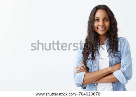 Glad young good looking Afro-American woman with clean dark skin and black long hair posing indoors with crossed arms, smiling broadly with white teeth, laughing at good joke, wearing denim shirt over #704020870