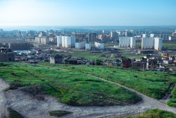 Glade of green grass on the background of large apartment buildings. House mortar in the city on a background of green grass.