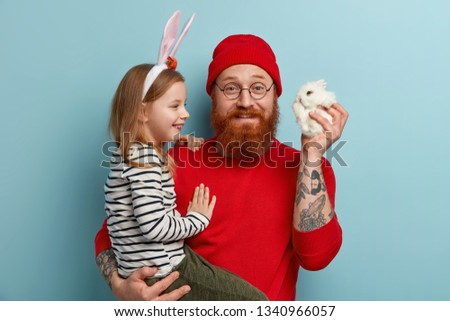 Gladful bearded father carries small daughter on hands, gives little decorative bunny, presents live pet to child, think out which name to give, stand over blue background. Childhood, domestic animals