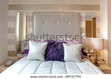 Glamerous bed dressed with brightly colored cushions and pillows with silver  textile headboard  Glamerous Bed. Silver Cushions Bedroom