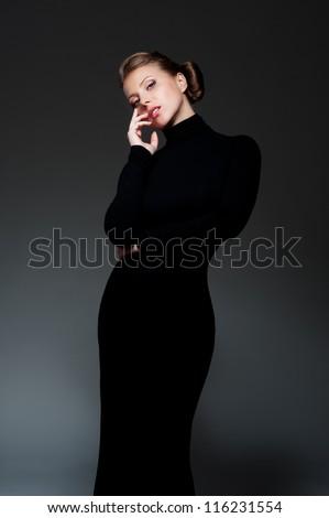 glamor woman in long black dress posing over dark background