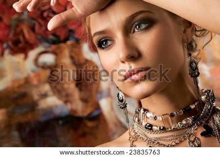 Glamorous. A portrait of a young glamorous woman wearing stylish necklace and pierced earrings. - stock photo