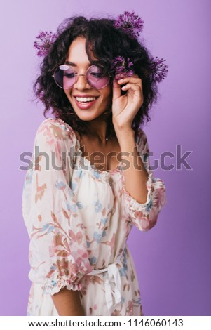 Glamorous african girl in glasses having fun during photoshoot with alliums. Indoor photo of positive female model in dress expressing happiness. #1146060143
