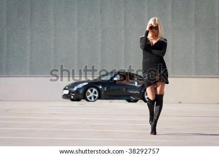 Stock Photo Glamorous blond babe near tuned supercar