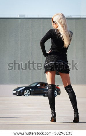 Stock Photo Glamorous blond babe near tuned supercar