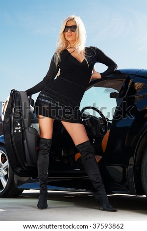 Glamorous blond babe standing near tuned supercar - stock photo